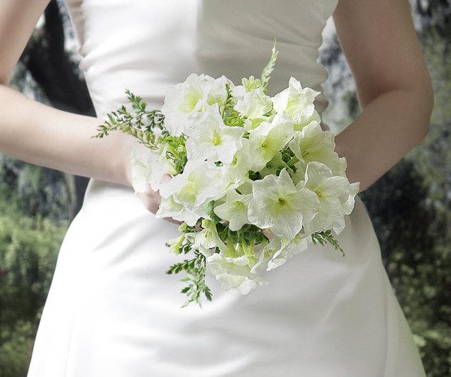 Noiva segurando seu buquê de flores.