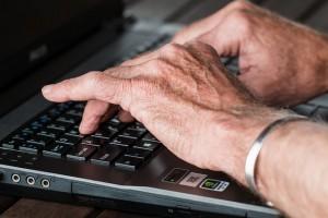 Mão de idoso teclando