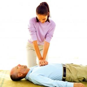 Mulher fazendo massagem cardíaca em homem com parada cardíaca.