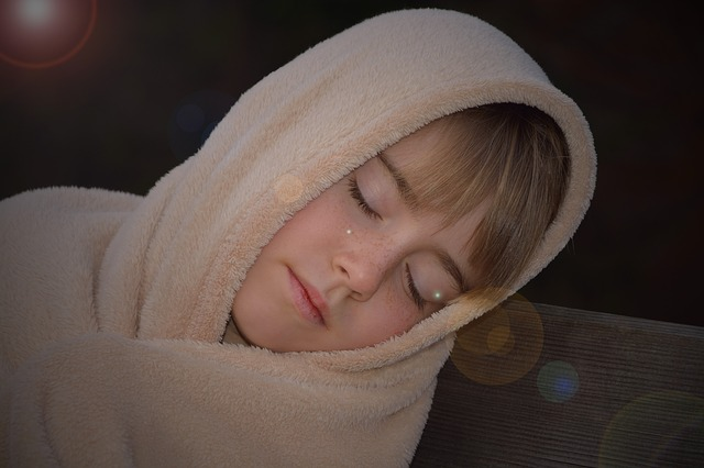 Criança dormindo num banco qualquer.